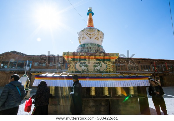 On 6 DEC, 2016. : White Tibetan pagoda and colorful prayer flags.Many people and Tradition Chinese building. Located in Guishan park, Old Town of Dukezong, Shangri-La, China.