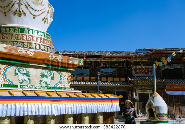 On 6 DEC, 2016. : White Tibetan pagoda and colorful prayer flags.People and Tradition Chinese building. Located in Guishan park, Old Town of Dukezong, Shangri-La, China.