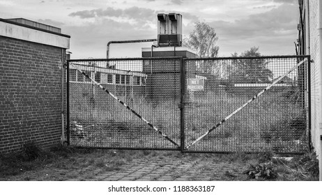 On an abandoned industrial site a big iron gate is locked towards a closed factory. It is located in the city of Almelo in the province of Overijssel, The Netherlands near the German border.