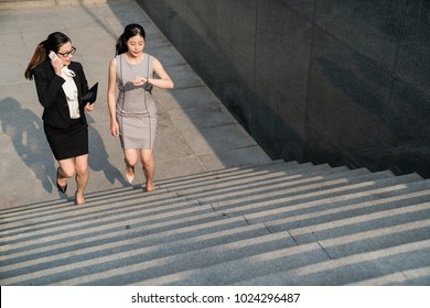 On an above view of Two business Asian lady walking upstairs. one speaking on the phone and one looking staring on the watch. They are going to attend a meeting.