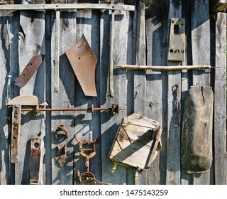 On the aged wooden l wall of the village shed barn  hang  used  old  rusty retro  agricultural tools. Sunny summer  day vintage background