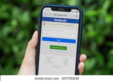 On April 19, 2018 at Bangkok, Thailand. A woman is holding smartphone with green plants background. She is singing in Facebook website. The picture concepts are technology, social network.
