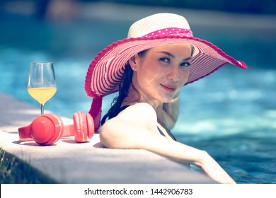 On Asian woman wearing red big hat standing in swimming pool with glass of orange juice and headphone, looking at camera with happiness face.