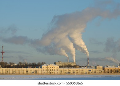 On the background of blue sky smoke rises from factory chimneys.