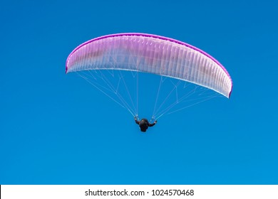 On the background of blue sky soars a glider white-pink color