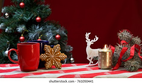on the background of a Christmas tree there is a two cups of coffee or tea on the tablecloth. there is a candle, ornaments, a Christmas gingerbread.Color photo.