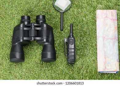 on the background of grass binoculars and a map to search for missing people