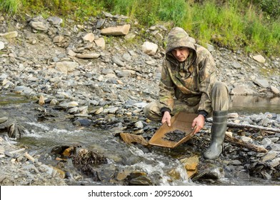 On the banks of the river with the help of geologist tray determines the content of gold in the rock.