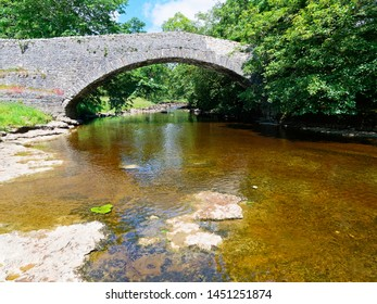 On the banks of the River Ribble watching the water flow under the old stone bridge near Stainforth in the Yorkshire Dales.