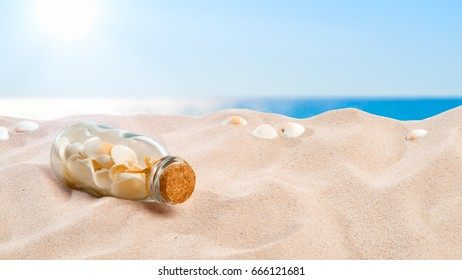 On the Beach - collection of shells in a bottle placed on a sand dune in front of beautiful azure sea