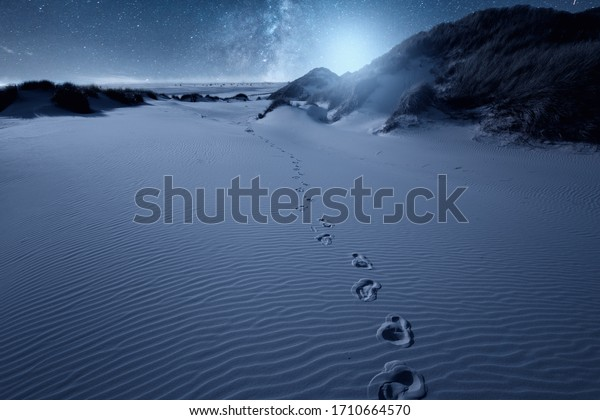 On the beach with the footprints and stars in the sky on the horizon. Milky way