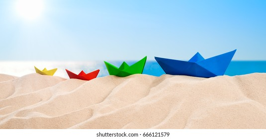 On the Beach - Four colorful paper boats on a sand dune in front of the beautiful sea on a sunny day