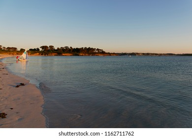 On a beach in Landeda, Brittany, as the sun begins to set a small sailing boat is pushed out in to the calm water.