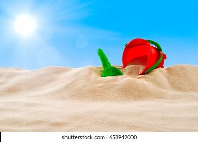 On the Beach - Sand dune with sand toys on a sunny day