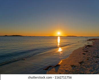 On a beach the setting sun reflects of the waters of the English Channel at Landeda, Brittany.