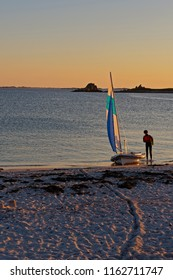 On a beach at sunset a man, back to camera, stands by a small yacht at the waters edge.
