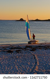 On a beach at sunset a man, back to camera, stands behind a small yacht at the waters edge.
