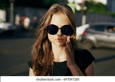 On a beautiful woman shines in the sun with glasses portrait, city
