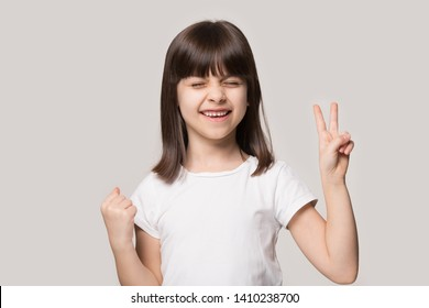 On beige studio background pose little girl in white tshirt got what she wanted feel excitement show V victory symbol, Yes gesture, demonstrating give peace sign, dream came true, celebration concept