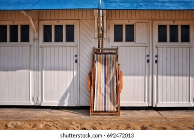 On the Belgian North Sea coast, there are a lot of beach cabins and beach chairs for the holidaymakers on the beach.
