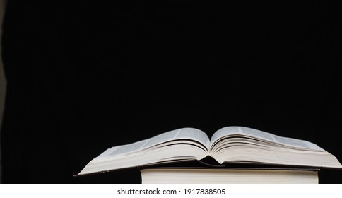 On a black background lies an open book. Concept education
