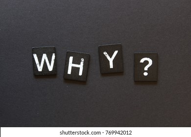 """WHY?"" on black tiles against black background."