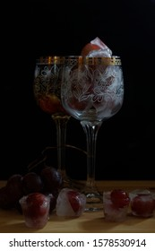 On a blackboard and a black background, two vintage glasses. In the foreground, a glass of ice cubes and grapes. In the background, a glass of white sparkling wine with grapes on the bottom. Next to t