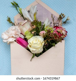 On a blue background, a beautiful bouquet of roses, iris and carnations, decorated in the form of an envelope