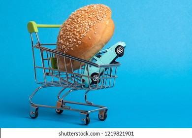 on a blue background cart from the supermarket in which a bun for a hamburger and a toy car, a solid blue background