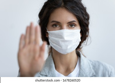 On blue background close up focus on female face in mask looking at camera, out of focus stretched hand. Help slow outbreak of corona virus, stay at home, keep distance and hygiene conceptual poster