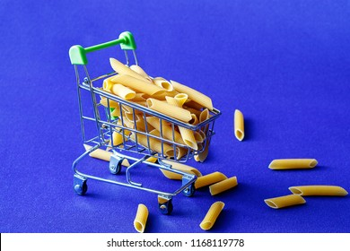 on a blue background a shopping cart from a supermarket in which there are pasta in the form of feathers, a piece of macaroni is scattered near the trolley