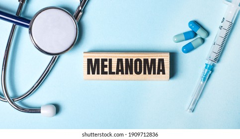 On a blue background, a stethoscope, a syringe and pills and a wooden block with the word MELANOMA. Medical concept