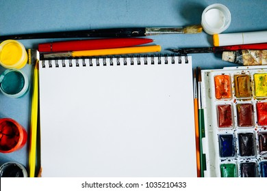 on a blue background there are paints, brushes, pencils and a sheet of white paper