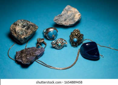 On a blue background are two rings and earrings. Nearby are semiprecious stones - agate, dumortierite, apatite, sadite.