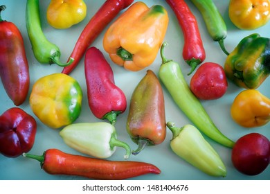 On the blue background of a variety of color and shape of the fruits of bell peppers of different varieties.