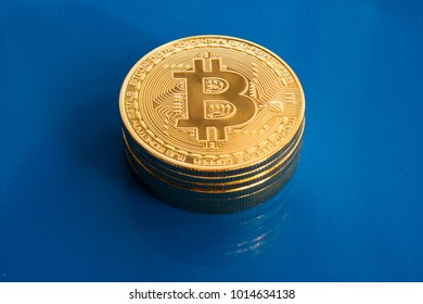 On a blue glass background are gold coins of a digital crypto  currency - bitcoins.