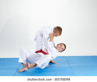 On a blue mats athletes train judo throws