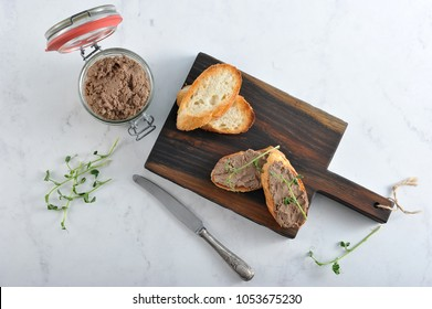 On the board are slices of fried baguette with liver pate. Next to the pot with pate, young greens of peas, a knife. Light background. View from above. Close-up.
