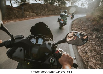 On board view of motorcycles turning on the road, from the point of view of the passenger.