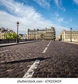 On a bridge with cobblestones in foreground and buildings of Paris in the background
