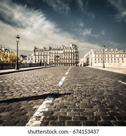 On a bridge with cobblestones in foreground and buildings of Paris in background, with vintage filter