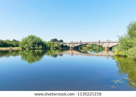 On a bright clear summer day a calm River Trent flows under the three arched Gunthorpe Bridge in Nottinghamshire.