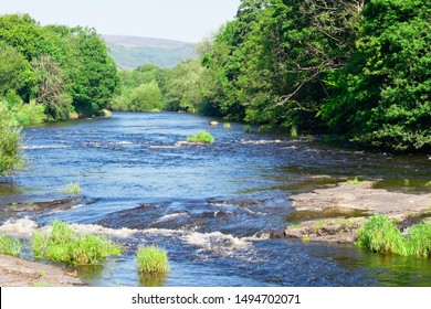 On a bright, hazy, summer day in Llangollen the River Dee flows fast over rocks creating small rapids.