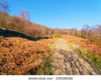 On a bright sunny day a footpath winds up hill between dry stone walls in the Derbyshire Peak District.