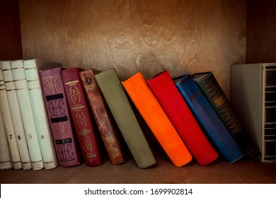 On a brown wooden shelf is a row of old classic thick colored books