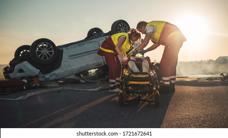 On the Car Crash Traffic Accident Scene: Paramedics Saving Life of a Female Victim who is Lying on Stretchers. They Listen To a Heartbeat, Apply Oxygen Mask and Give First Aid. Background Firefighters