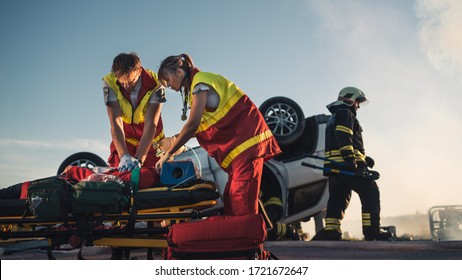 On the Car Crash Traffic Accident Scene: Paramedics Saving Life of a Female Victim who is Lying on Stretchers. They Apply Oxygen Mask, Do Cardiopulmonary Resuscitation / CPR and Perform First Aid