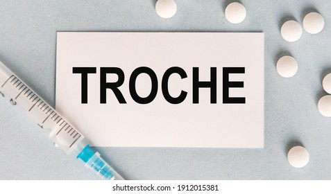 On the card text TROCHE, next to white tablets and a syringe.