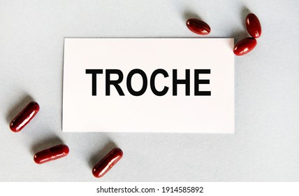 On the card the text of TROCHE, next to the sculpted red capsules.
