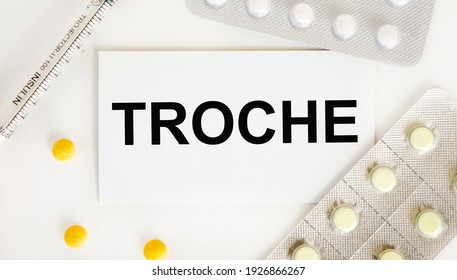 On the card text TROCHE, next to blisters with tablets and a syringe.